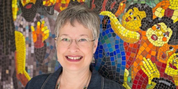 Nina Miller's photographic portrait of Lynn Bridge in front of her mosaic wall in Austin, Texas