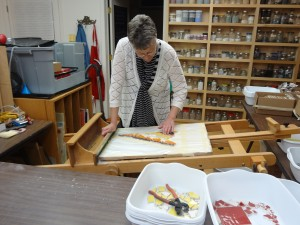 Lynn Bridge checking a mosaic project in her art studio